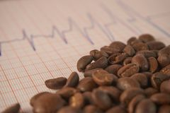 Loose roasted coffee beans on an ECG tracing stock images