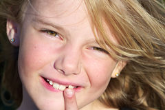 Loose tooth. A pretty blond girl showing off her loose tooth Royalty Free Stock Image