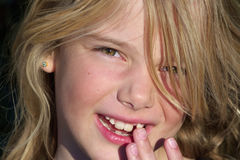 Loose tooth. A pretty blond girl showing off her loose tooth Royalty Free Stock Photos