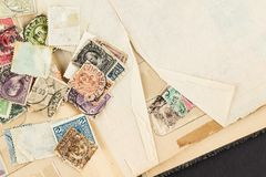 Free Loose Vintage Postage Stamps On Book Royalty Free Stock Photos - 149980508