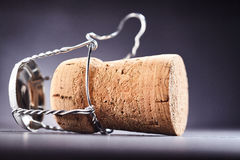 Loosened metal wire around wine bottle cork. Over dark background for concept about alcoholic drinks Royalty Free Stock Images