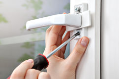 Loosening the screw handles plastic window with a hand tool. Stock Image
