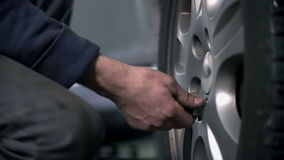 Loosening the screw on a tire. Vulcanisers unscrewing the rims and changing the tires stock footage