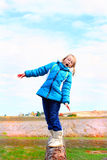 Loosing Balance. A cute little blond 9 year old girl wearing glasses and a warm blue winter hoody coat and boots standing loosing her balance on a log. Farmland Stock Image