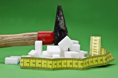 Loosing weight. A hammer which is disturbing sugar cubes for a healthier nutrition in the future Stock Photography