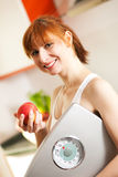 Loosing weight - woman with scale and apple Stock Photography