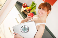Loosing weight - woman with scale and apple Royalty Free Stock Images