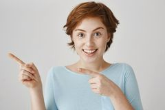 Loot at that direction. Beautiful caucasian redhead with freckles pointing left with forefingers and smiling broadly. Being up to something funny and good stock photos
