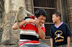 Lopburi, Thailand: Affe, der auf der Schulter des Mannes sitzt Stockfoto