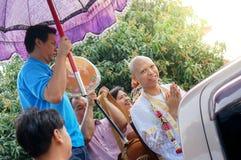LOPBURI THAILAND - MARS 6, 2016 a-mannen som genomgår buddistisk prästvigning, förbereder sig att medföljas av lokalen ståtar Arkivbild