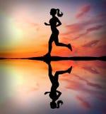 Lopend meisje bij zonsondergangsilhouet Royalty-vrije Stock Afbeelding