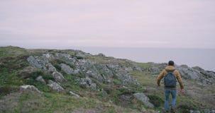 Lopend op de bovenkant van berg jonge kerel hield hij die de het bergrotsen en landschap onderzoeken, hij op de bovenkant op van stock videobeelden