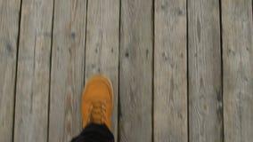 Lopend op een pijler bij het strand, POV van een mens met gele schoenen wordt geschoten die stock footage