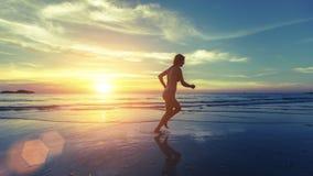 Lopend silhouet van jong meisje op het overzeese strand tijdens een verbazende zonsondergang stock fotografie