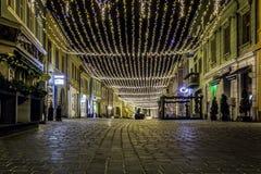 Lopend straat met Kerstmislichten tijdens de nacht - 6 December, 2015 in de middeleeuwse stad van de binnenstad van Brasov, Roeme Royalty-vrije Stock Foto's