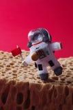 Lopende astronaut, rode achtergrond Het gloeilampenkarakter kleedde zich in spacesuit en ruimtevaardersmunitie Kosmonaut met Stock Foto's