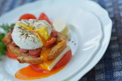 Lopende eierdooier op sandwich met worst, brood, kaas, tomaat op witte plaat dicht Stock Fotografie