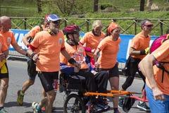 Lopende Engelen die een mens in rolstoel in het de Marathonras van Rome vervoeren van 2019 stock foto's