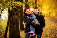 Lopende familie met twee kinderen in herfstpark stock foto's