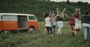 Lopende groep modieuze vrienden in het midden van gebied, achter een retro oranje bestelwagen stock video