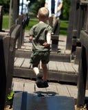 Lopende jongen op speelplaats Stock Foto's