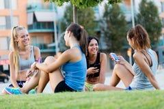 Lopende meisjes die pret in het park met mobiele telefoon hebben Royalty-vrije Stock Afbeeldingen
