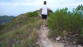 Lopende mens op bergweg Sportfitness jongen die buiten in berg uitoefenen stock footage