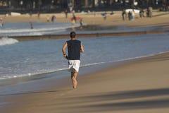Lopende mens op de kust stock foto