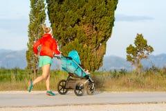 Lopende moeder met wandelwagen die van moederschap genieten bij zonsondergangland royalty-vrije stock fotografie