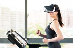 Lopende tredmolen van de schoonheids de Aziatische vrouw door VR hoofdtelefoonglazen Stock Fotografie