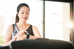 Lopende tredmolen van de sport de Aziatische vrouw smartwatch aan het luisteren mus Stock Foto's