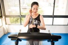 Lopende tredmolen van de sport de Aziatische vrouw smartwatch aan het luisteren mus Royalty-vrije Stock Afbeeldingen
