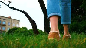 Lopende vrouw in de stad, aardig groen gras, langzame motie stock footage