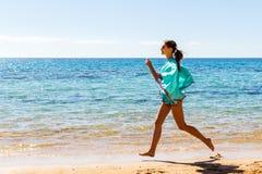 Lopende vrouw op bech Vrouwelijke agent die tijdens openluchttraining op strand aanstoot royalty-vrije stock afbeelding
