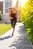 Lopende vrouw in zwarte sportuitrusting op de stoep Royalty-vrije Stock Fotografie