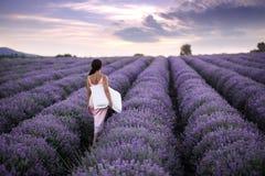 Lopende vrouwen op het gebied van lavendel Romantische vrouwen op lavendelgebieden Het meisje bewondert de zonsondergang op laven royalty-vrije stock afbeeldingen