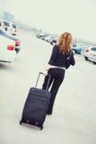 Lopp: Bakre sikt av kvinnan som går till och med parkeringsplats Arkivfoto