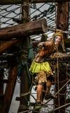 Lopp för hinder för tuff grabb för konkurrent 2014 för toppen hjälte i maskeradkläderna som hänger på rep Royaltyfria Bilder