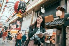 Lopp för resehandbok för kvinnahandelsresandeinnehav i Japan royaltyfri foto