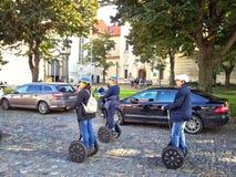 Lopp för tre turister Prague på segways Arkivbild