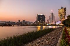 Lopp för underhållning för gränsmärke för byggnad för för solnedgångCityscapekasino och hotell modern och ekonomizon av den Macao Royaltyfri Foto