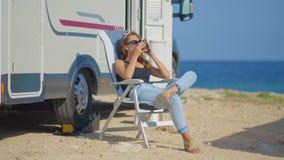 Lopp i motorhome Resa kvinnan vid mobila det campervan motorhemmet RV Dricka kaffe f?r kvinna lager videofilmer