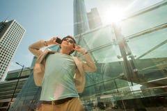 Lopp- och livsstilbegrepp Dana mannen som lyssnar till musik på telefonen och dansar mot bakgrunden av skyskrapor royaltyfri fotografi
