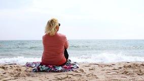 Lopp och semester Den vuxna blonda kvinnan sitter på havet och kopplar av stock video