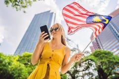 Lopp och teknologi Turisten för den unga kvinnan med flaggan av Malaysia ser en stadsöversikt i en smartphone för arkivbild