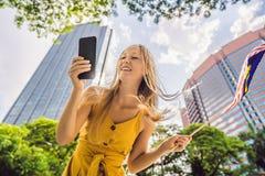 Lopp och teknologi Turisten för den unga kvinnan med flaggan av Malaysia ser en stadsöversikt i en smartphone för royaltyfri fotografi