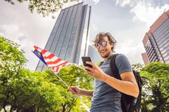 Lopp och teknologi Turisten för den unga mannen med flaggan av Malaysia ser en stadsöversikt i en smartphone för royaltyfri foto