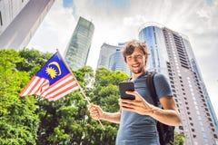 Lopp och teknologi Turisten för den unga mannen med flaggan av Malaysia ser en stadsöversikt i en smartphone för royaltyfria foton