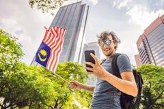 Lopp och teknologi Turisten för den unga mannen med flaggan av Malaysia ser en stadsöversikt i en smartphone för royaltyfri bild