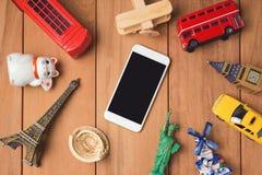 Lopp- och turismbegrepp med smartphonen och souvenir från hela världen royaltyfria bilder